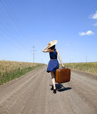 Lonely girl with suitcase at country road. Royalty Free Stock Images