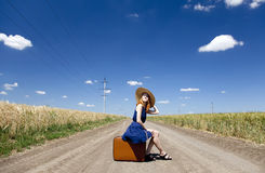 Lonely girl with suitcase at country road. Stock Image