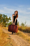 Lonely girl with suitcase at country road Stock Photo