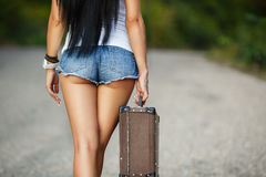 Lonely Girl with a suitcase on a country road ... Woman body in jean shorts. The model is back.Lonely girl with suitcase at country road royalty free stock photography