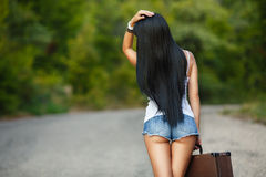 Lonely Girl with a suitcase on a country road ... Woman body in jean shorts. The model is back.Lonely girl with suitcase at country road royalty free stock photos