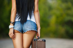 Lonely Girl with a suitcase on a country road ... Woman body in jean shorts. The model is back.Lonely girl with suitcase at country road stock photo