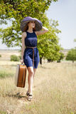 Lonely girl with suitcase at countryside. Royalty Free Stock Image