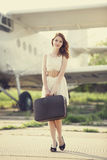 Lonely girl with suitcase at near airplane. Royalty Free Stock Image