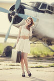 Lonely girl with suitcase at near airplane. Royalty Free Stock Photos