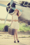 Lonely girl with suitcase at near airplane. Royalty Free Stock Images