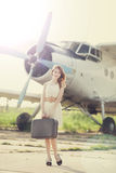 Lonely girl with suitcase at near airplane. Stock Image