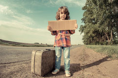 Lonely girl with suitcase. Standing about road and holding paper with copy space in hands Stock Photography