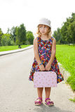 Girl with suitcase standing on road Stock Images
