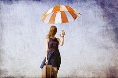 Lonely girl with suitcase and umbrella. Stock Photos