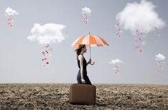 Lonely girl with suitcase and umbrella at countryside field. Lonely girl with suitcase and umbrella at countryside field with couds and clothes rain Royalty Free Stock Images