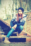 Lonely girl teenager in hat sitting on stairs and sad autumn. Outdoors Royalty Free Stock Photography