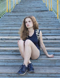 Lonely girl teenager sitting on stairs stock photo