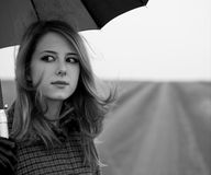 Lonely girl with umbrella at country road. Royalty Free Stock Photography