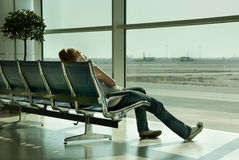 Lonely girl waiting in airport. A lonely and jetlagged girl sitting and sleeping in a seats row in front of a sunny window facing the tarmac and airplanes on an Royalty Free Stock Photos
