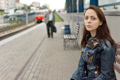 Lonely girl waiting in an urban railway station Royalty Free Stock Image