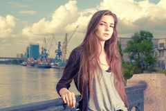 Lonely girl waiting for your. Wearing light gray shirt, black jacket, an young american woman standing by metal fence on Royalty Free Stock Photos