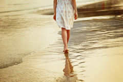 A lonely girl is walking along island coastline. And has reflection on wet sand Royalty Free Stock Images