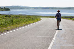 Lonely girl walking along the middle of the road on the background of the sea and the rural landscape. Stock Photography
