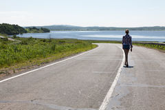 Lonely girl walking along the middle of the road on the background of the sea and the rural landscape. Royalty Free Stock Images