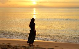 Lonely girl walking on the beach at the sunset Royalty Free Stock Photography