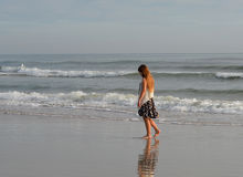 Lonely girl walking on beach. Royalty Free Stock Image