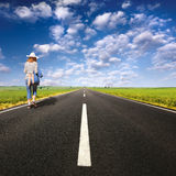 Lonely girl walking on empty road Stock Images