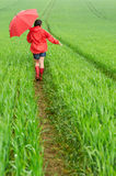 Lonely girl walking in the rain Stock Image