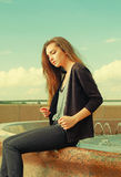 Lonely girl wants someone to talk. Wearing light gray sweater, black pants, an youg american woman sitting on red Royalty Free Stock Photo