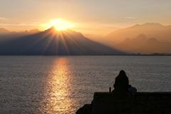 Lonely girl is watching sunset. Royalty Free Stock Photo