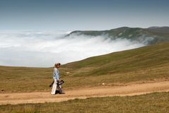A lonely girl with a camera and a tripod is walking along a wild mountain road above the clouds stock photography
