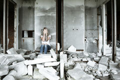 A lonely girl in a white T-shirt and jeans sits on the ruins of a ruined house. Sad expression, tragic atmosphere. Russia Royalty Free Stock Images