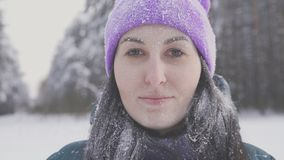 Lonely girl in the woods smiling looking at the camera, covered with snow after a snow storm. Close up Stock Image