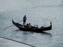 Lonely gondola at sea. Gondolier steers the boat, and a loving couple enjoys recreation Stock Photography