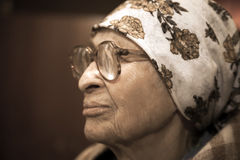 Lonely grandma in scarf and glasses. Elderly woman in scarf and glasses at home stock images