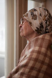 Lonely grandma. In scarf and glasses looking aside stock images