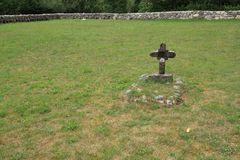 Lonely grave. Old lonely grave with concrete cross in the military cemetery in Soča. Here Austrian soldiers from wwi lies under the lawn Royalty Free Stock Images