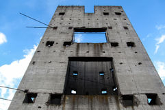 A lonely gray wall against the blue sky. Concrete wall with the holes in which the sky shines Stock Image