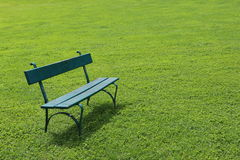 Lonely green bench on short cut grass Stock Image