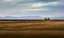 Lonely green roof cottage in yellow grass filed with mountain range background Stock Photos