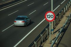 Lonely grey car on highway and SPEED LIMIT sign in Madrid. Lonely grey car passing through multi lane highway and SPEED LIMIT signpost, on sunset in Madrid royalty free stock photos