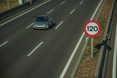 Lonely grey car on highway and SPEED LIMIT signpost in Madrid. Lonely grey car passing through multi lane highway and SPEED LIMIT signpost, on sunset in Madrid royalty free stock photography