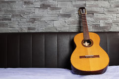 Lonely guitar standing ob bed Royalty Free Stock Images