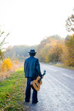 Lonely guitarist looking at empty country road in. Copy space pcture of lonely guitarist in denim suit and hat looking at  empty country road in autumn Stock Photo