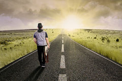 Lonely guitarist walking on road 1 Stock Photos