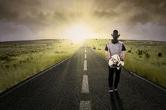 Lonely guitarist walking on road. The lonely guitarist walking on road, shot outdoors at dusk Royalty Free Stock Photos