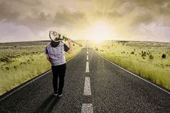Lonely guitarist walking on road 3 Royalty Free Stock Photography