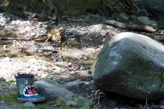 Lonely gum boots at the shore of the river next to the large roc royalty free stock photos