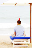 Lonely guy in hat on beach from behind Royalty Free Stock Photography