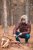 A lonely guy sharpens wooden blocks with a sharp knife. In forest. A young lonely guy sharpens wooden blocks with a sharp knife in a cold autumn forest Stock Photo